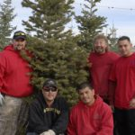 Big M Services team standing in front of Christmas Tree