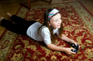 Child laying on an area rug playing video games