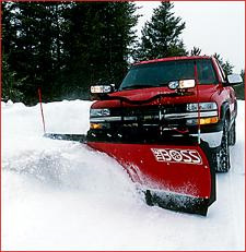 Red truck plowing snow off driveway