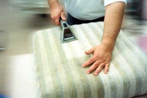 Man cleaning couch cushion with special vacuum